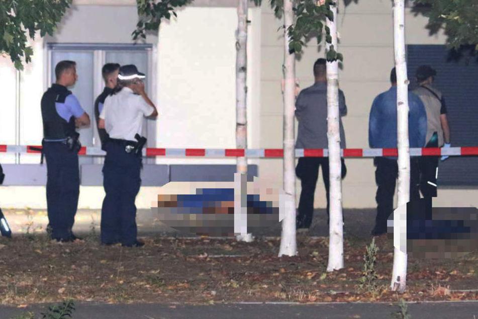 Die Polizei sichert den Bereich und deckt die toten Körper ab.