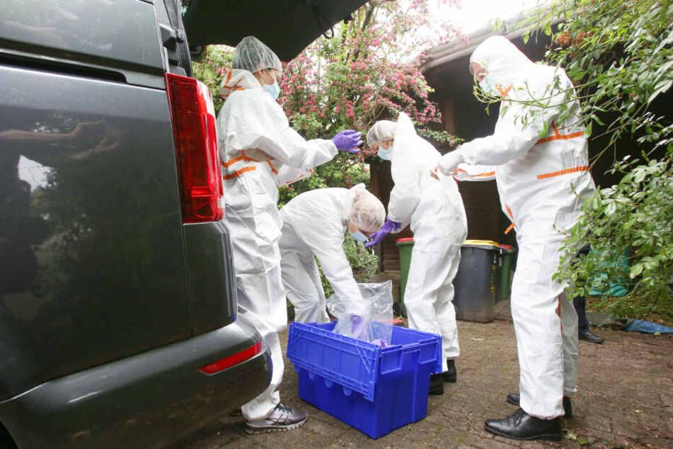 In weißen Schutzanzügen machen sich Ermittler der Mordkommission bereit, den Tatort zu untersuchen.