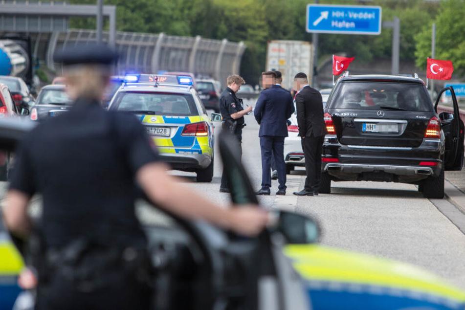 Polizisten kontrollieren Mitglieder des gestoppten Hochzeitskorsos.