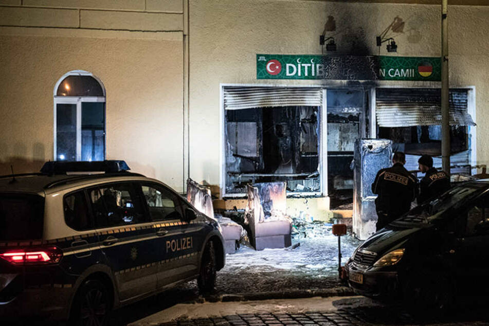 Polizeibeamte stehen vor den ausgebrannten Räumen in einem Haus an der Kühleweinstraße, in dem ein Moscheeverein untergebracht ist.