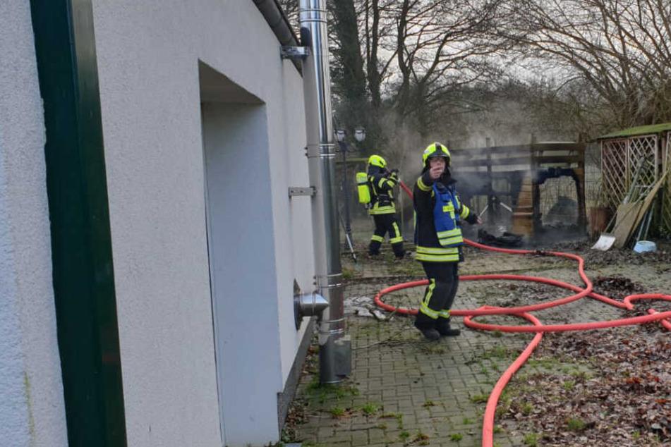 Feuerwehrleute löschen die brennende Hundehütte.