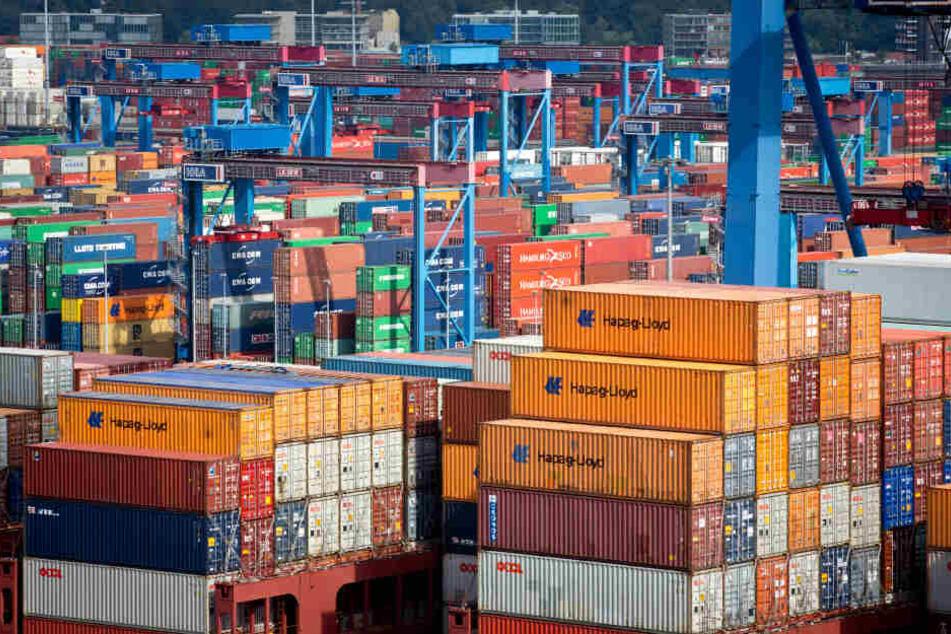 Ein hoch mit Containern beladene Containerschiff der Reederei Hapag-Lloyd liegt am Terminal Burchardkai im Hafen von Hamburg.