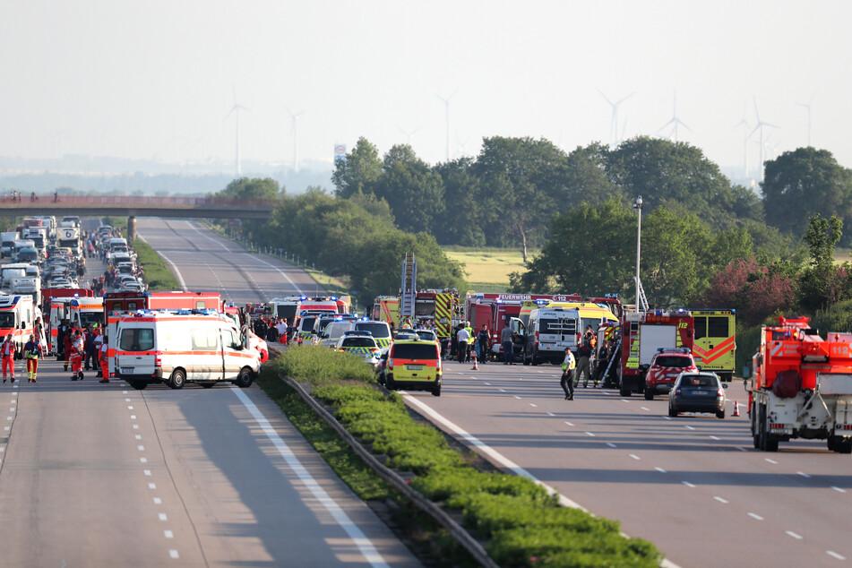 Einsatzkräfte der Feuerwehr und Rettungsdienst stehen bei einem Unfall bei Leipzig von einem verunglückten Bus.