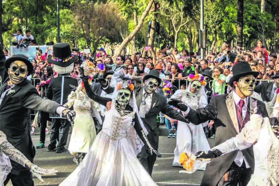 Geweint wird hier nicht: In Mexiko ist der Tag der Toten einer der wichtigsten Feiertage. In Mexiko City gibt es eine große Straßenparade mit Skeletten und dem Sensenmann.