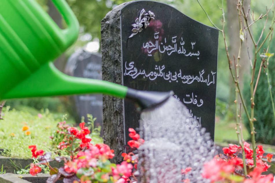 Ein Grabstein eines Muslimen ist mit Blumen geschmückt.