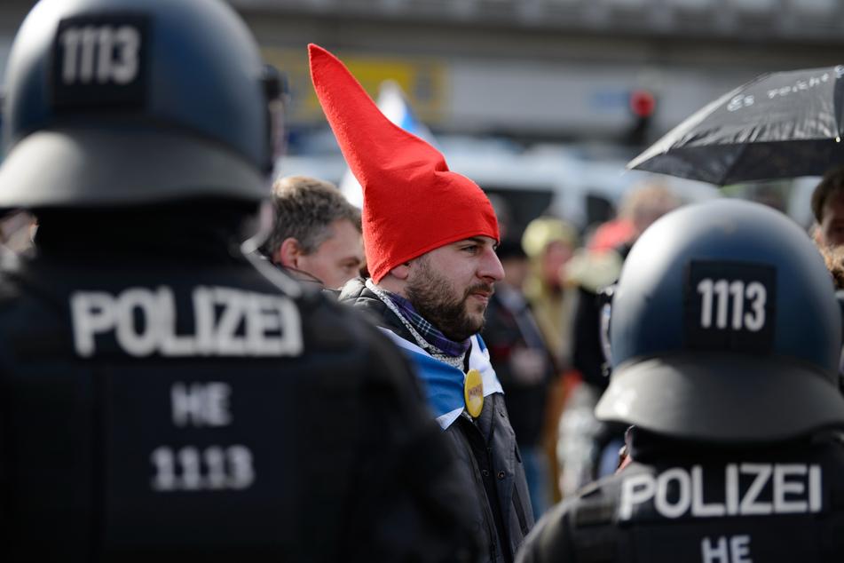 """Ein Teilnehmer mit einer roten Zipfelmütze und ohne Mund-Nasen-Bedeckung steht bei einer Kundgebung unter dem Motto """"Freie Bürger Kassel - Grundrechte und Demokratie"""" vor Polizisten."""