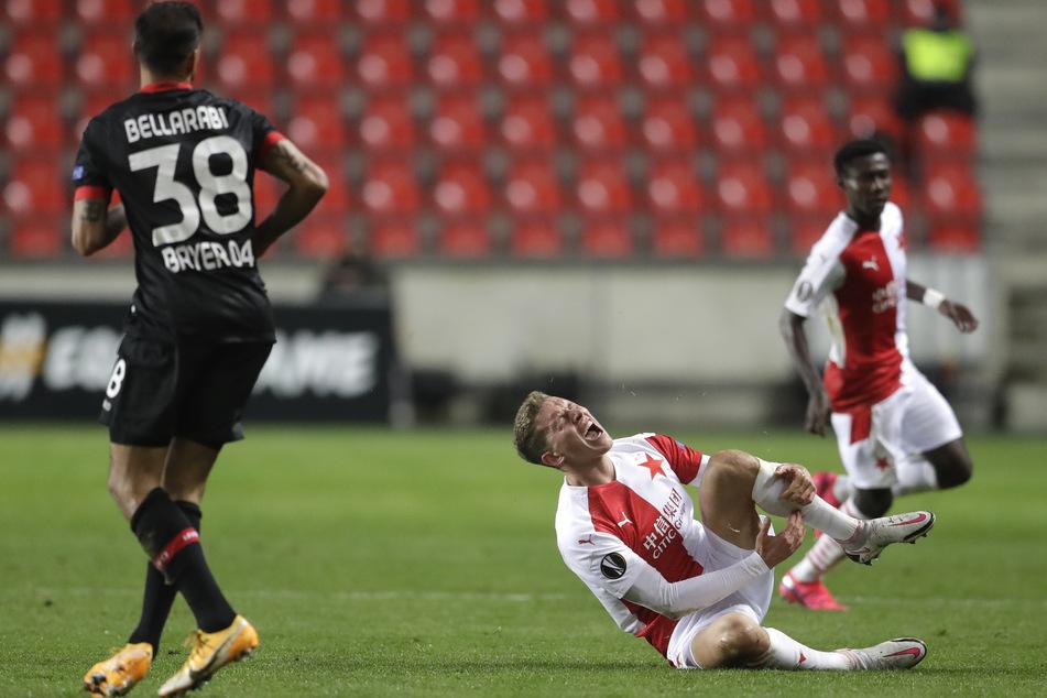 Slavias Lukas Provod (r) hält sich nach einem Foul von Leverkusens Karim Bellarabi das Schienbein.