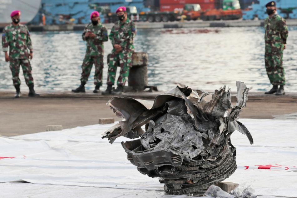 Indonesische Marinesoldaten betrachten ein Trümmerteil, das aus den Gewässern vor der Insel Java geborgen wurde.