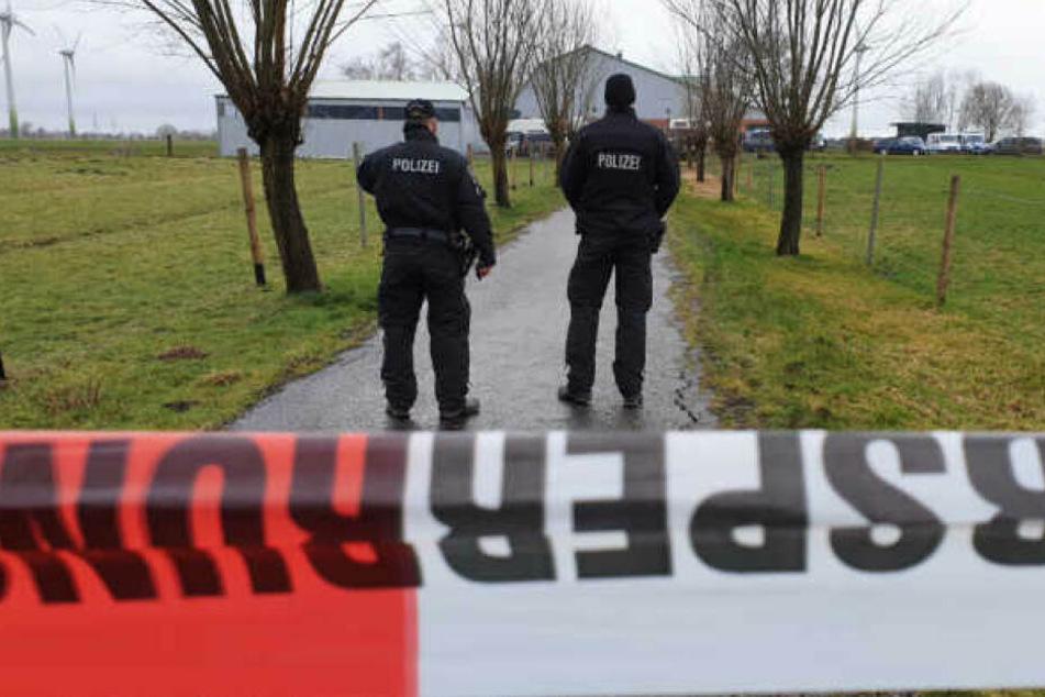 Polizisten sperren den Bauernhof in Dammfleth während der Durchsuchung ab.