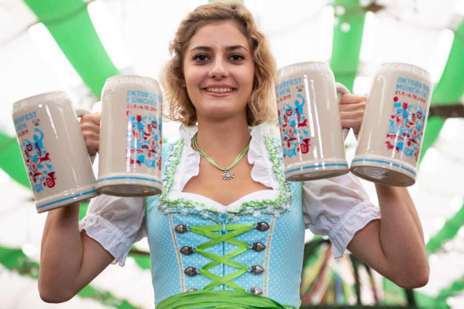 Elena Weidlich präsentiert im Armbrustschützenzelt auf dem Oktoberfestgelände den offiziellen Wiesn-Maßkrug 2019.