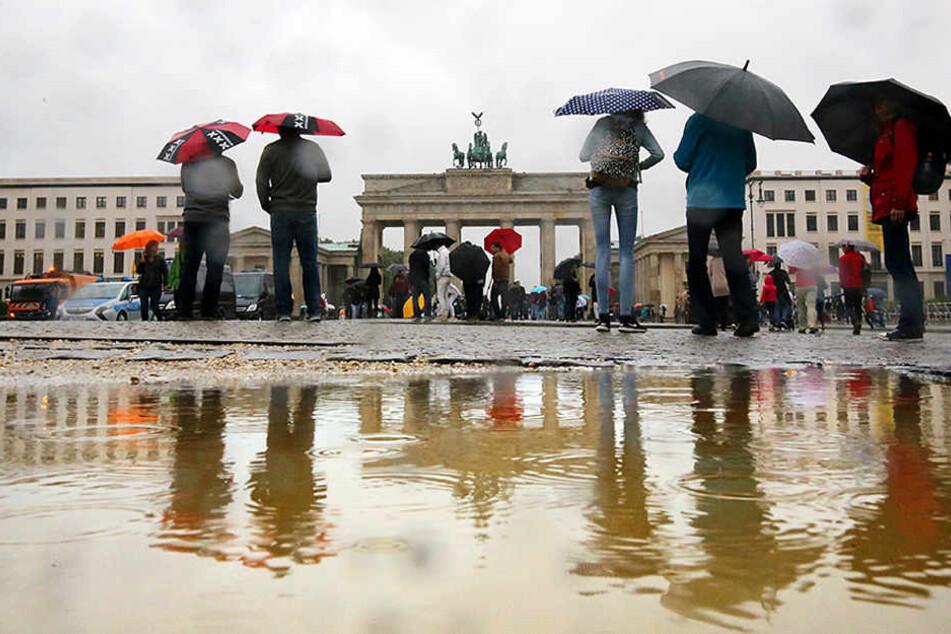 Bei ströhmendem Regen gehen Touristen bei Temperaturen um 16 Grad Celsius am Brandenburger Tor in Berlin vorbei.