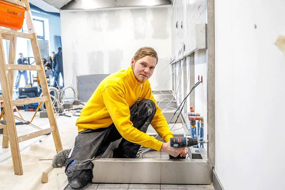 Monteur Manuel Thomke (22) arbeitet im Inneren an der Kochstrecke der Küche.