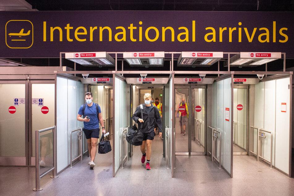 Passagiere mit Mundschutz kommen auf dem Flughafen London Gatwick an.