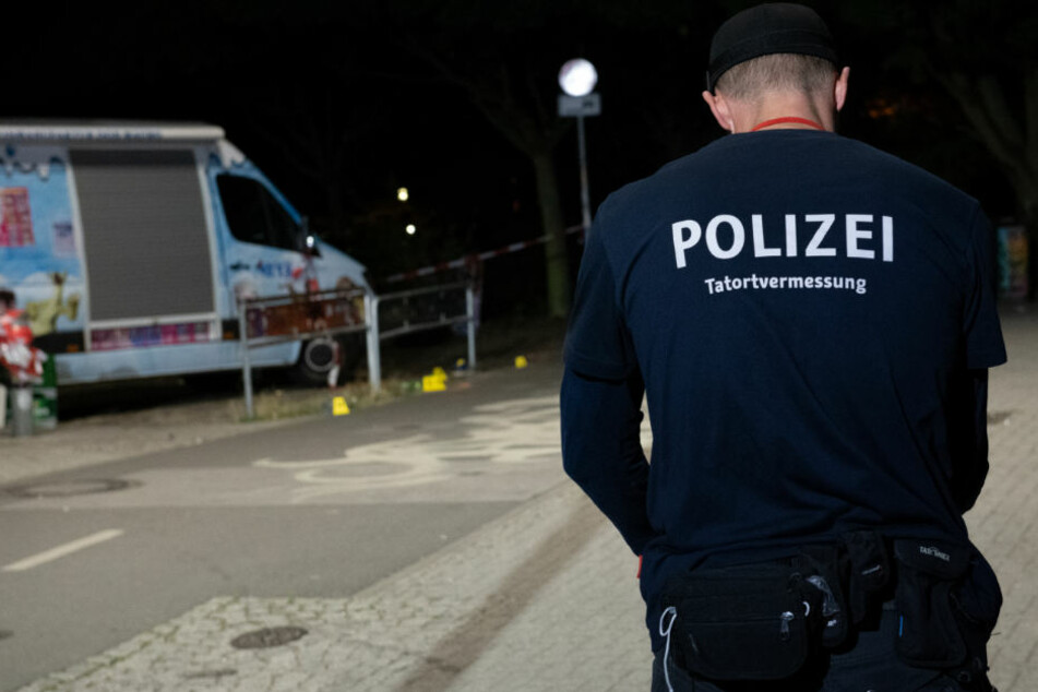 Ein Kriminaltechniker steht an einem Zugang zum Tempelhofer Feld in Berlin-Neukölln.