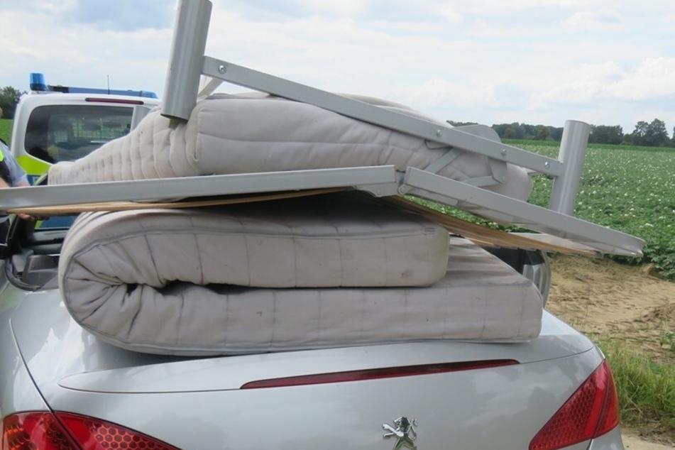 Der Fahrer (48) des Cabrios hatte ein Bettgestell und zwei Matratzen völlig ungesichert auf das Peugeot-Cabrio gelegt.