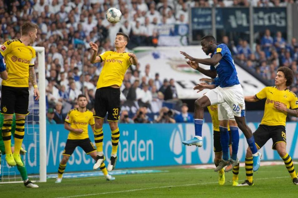 Schalkes Salif Sane (2.v.r.) und Julian Weigl von Dortmund versuchen an den Ball zu kommen.