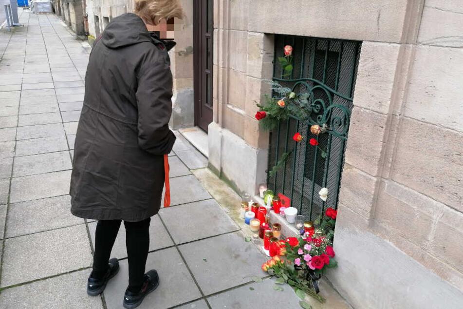 Eine Frau bleibt an der Stelle stehen, an der mittlerweile Kerzen und Blumen an das Opfer erinnern.