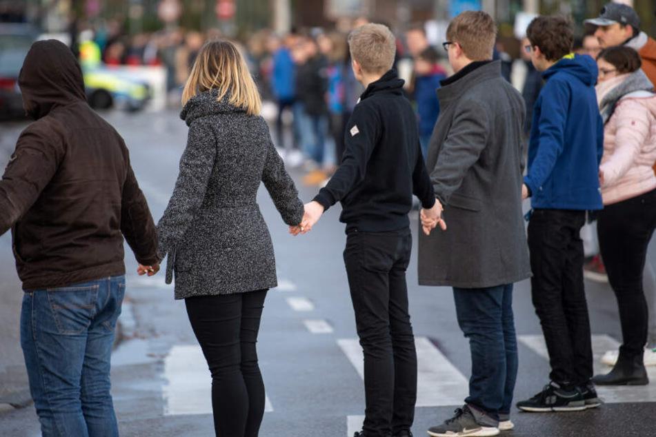 Schüler stehen während der Gedenkfeier in einer Menschenkette.