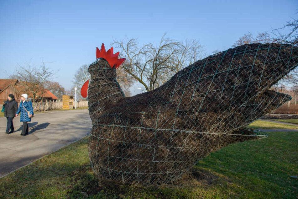 Besucher gehen auf der ega in Erfurt (Thüringen) an einer Hühnerfigur aus Erde und Metallgitter vorbei, die derzeit unbepflanzt ist.