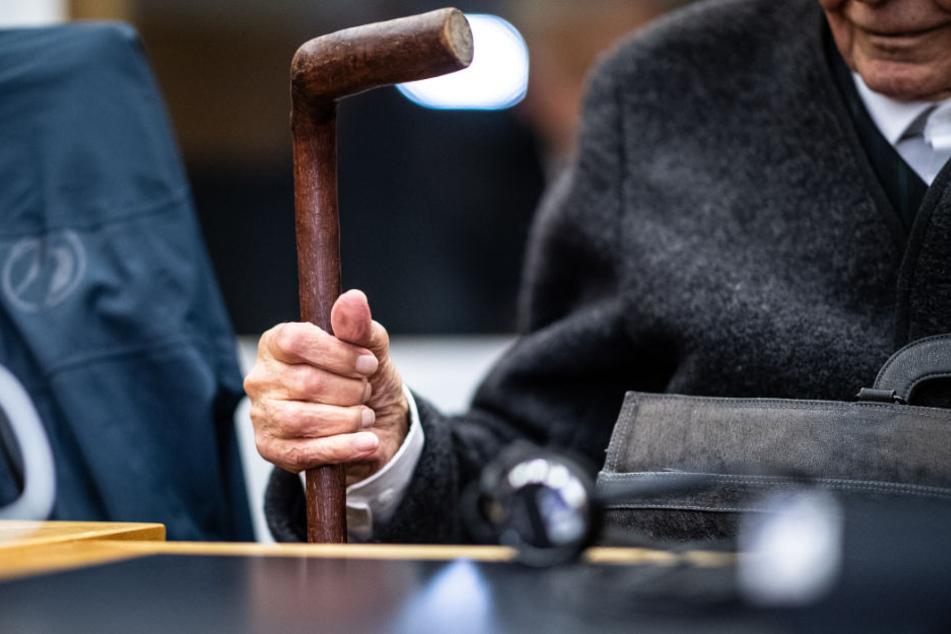 Auf der Anklagebank muss sich der 94-Jährige an einem Stock festhalten.