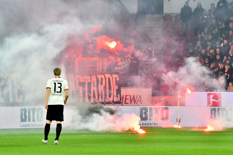(Leider) schon fast gewohntes Bild: Die Eintracht-Fans warfen vor dem Anpfiff mit Pyrotechnik umher. Frankfurts Martin Hinteregger (Li.) betrachtet das unschöne Spektakel.