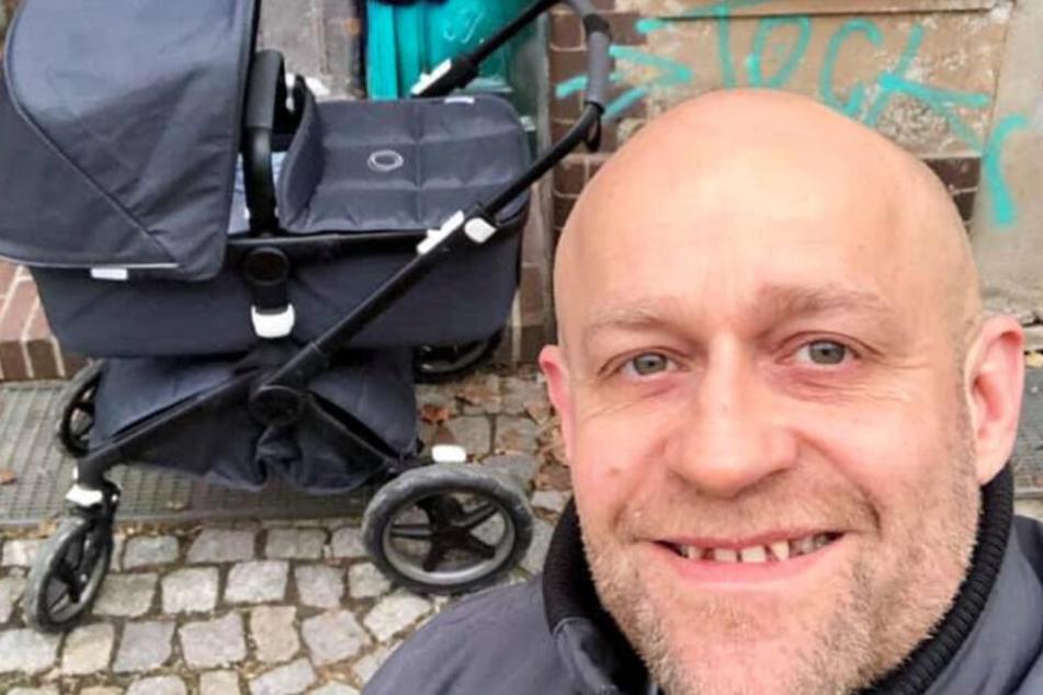 Jürgen Vogel präsentiert sich stolz mit Kinderwagen.