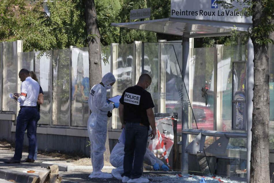 Polizisten untersuchen  eine Bushaltestelle, wo ein Auto einen Fußgänger angefahren und getötet haben soll.