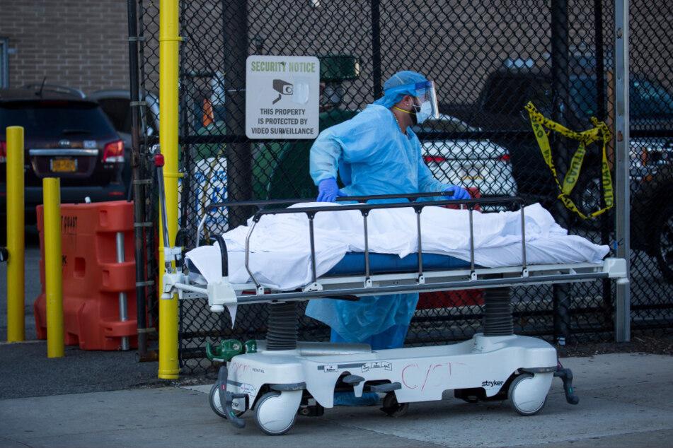 Ein medizinischer Mitarbeiter überführt den Leichnam eines Opfers, das in einem Krankenhaus an dem Coronavirus gestorben ist.