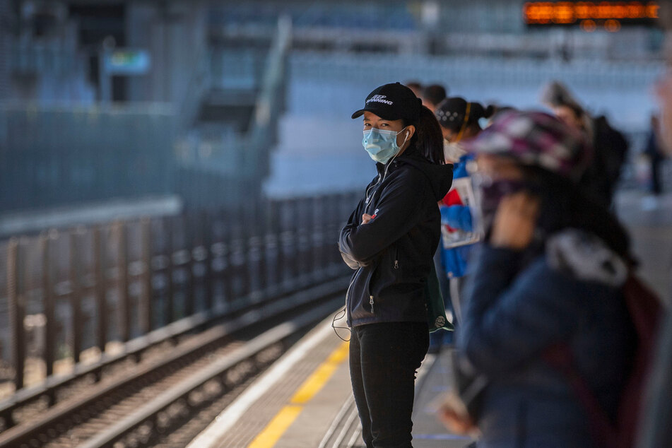 Fahrgäste stehen auseinander und tragen Gesichtsmasken auf einem Bahnsteig in der Londoner U-Bahn-Station. (Archivbild)