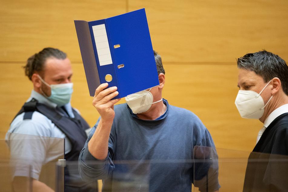 Der Angeklagte (48, M.) betritt im Beisein eines Justizbeamten und seines Verteidigers den Saal vom Landgericht.