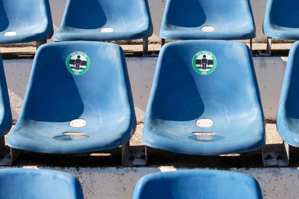 Schilder auf den Sitzplätzen an der Bremer Brücke in Osnabrück zeigen, wo die Fans sich hinsetzen sollen. Zunächst fällt das Eröffnungsspiel aus - es kommen also erstmal keine Anhänger ins Stadion.