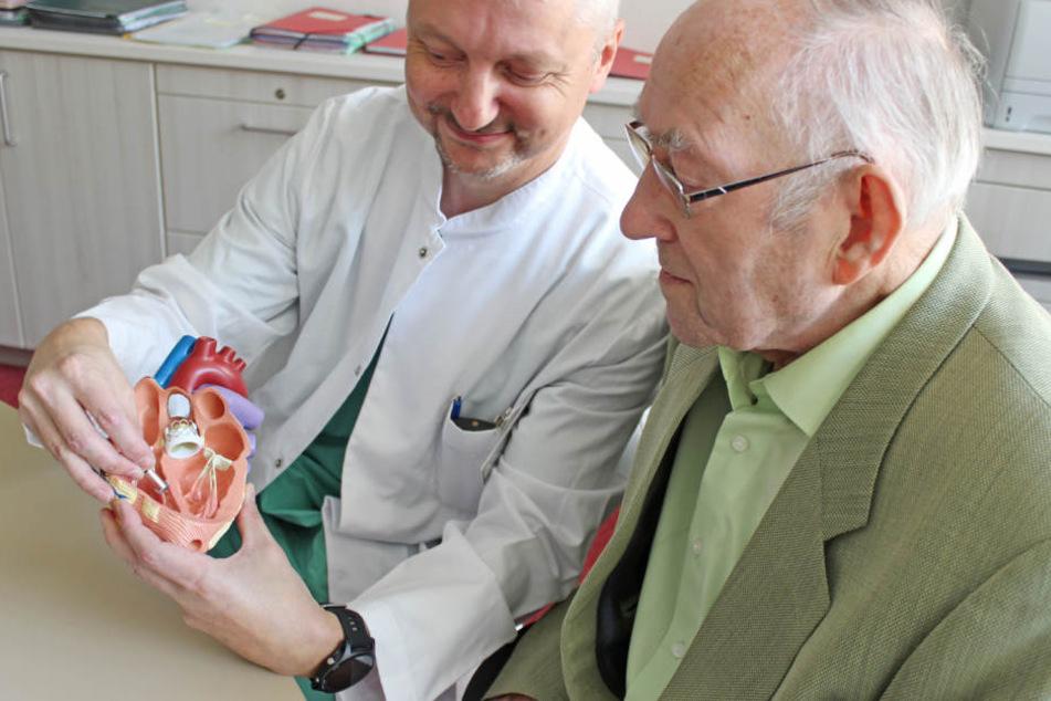 Oberarzt Marc Schönweiß erklärt Werner Milde (87), wo das kleine Wunderwerk eingesetzt wurde.