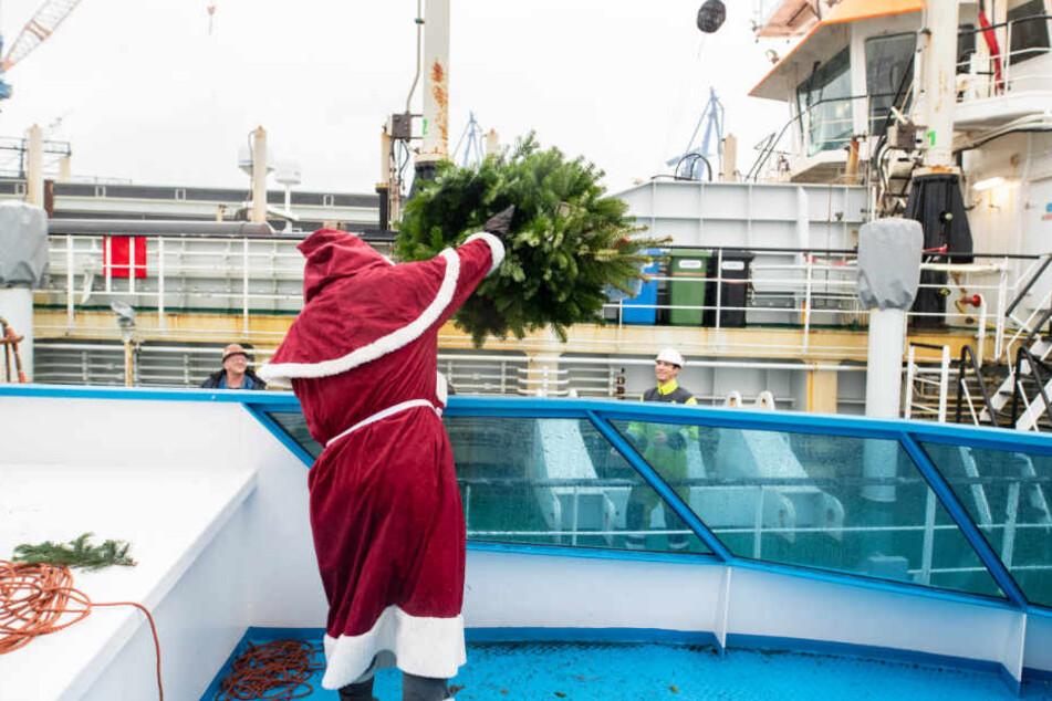 Mit Schwing wirft der Weihnachtsmann die Tanne von einem Schiff zum anderen.