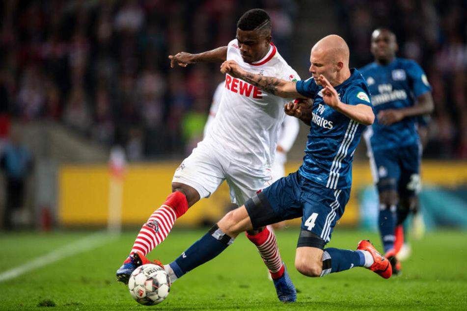 HSV-Kante Rick van Drongelen senst Kölns Stürmer Jhon Cordoba an der Seitenlinie um und bekommt dafür die gelbe Karte.