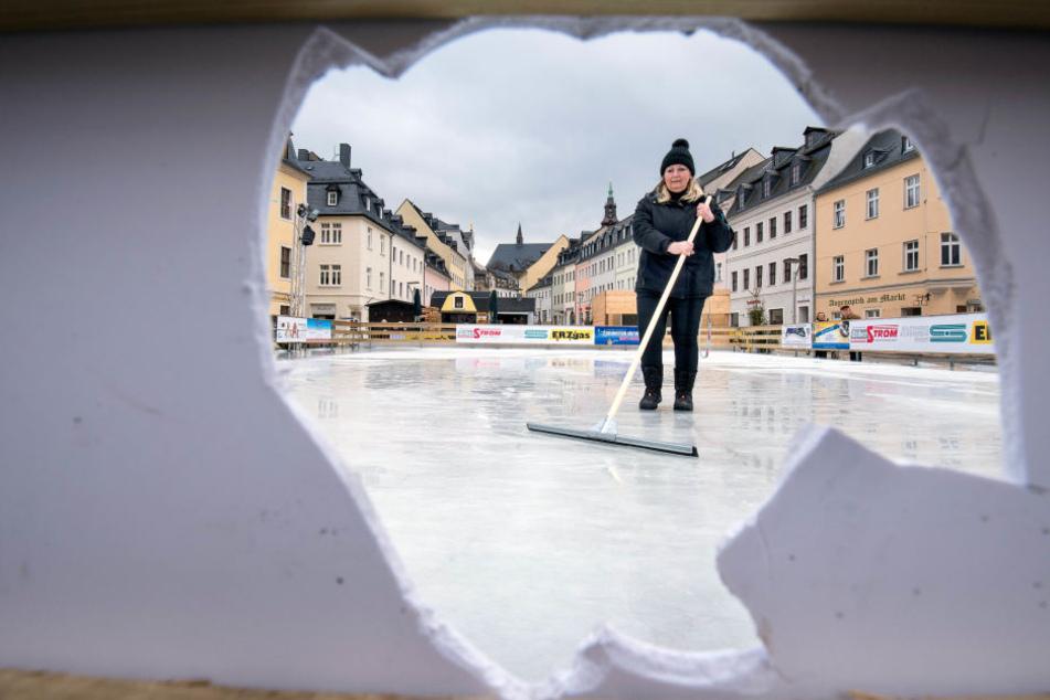 Auch an der Bande klaffen Löcher. Steffi Heidel (58) von den Stadtwerken entfernt Glassplitter vom Eis.