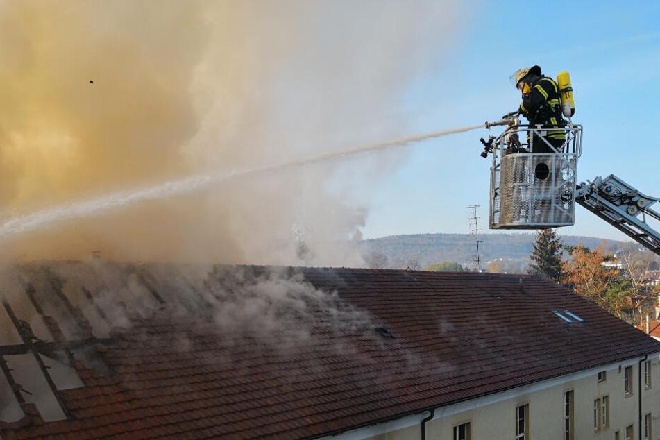 Ein Feuerwehrmann hält einen Wasserschlauch auf das brennende Haus.