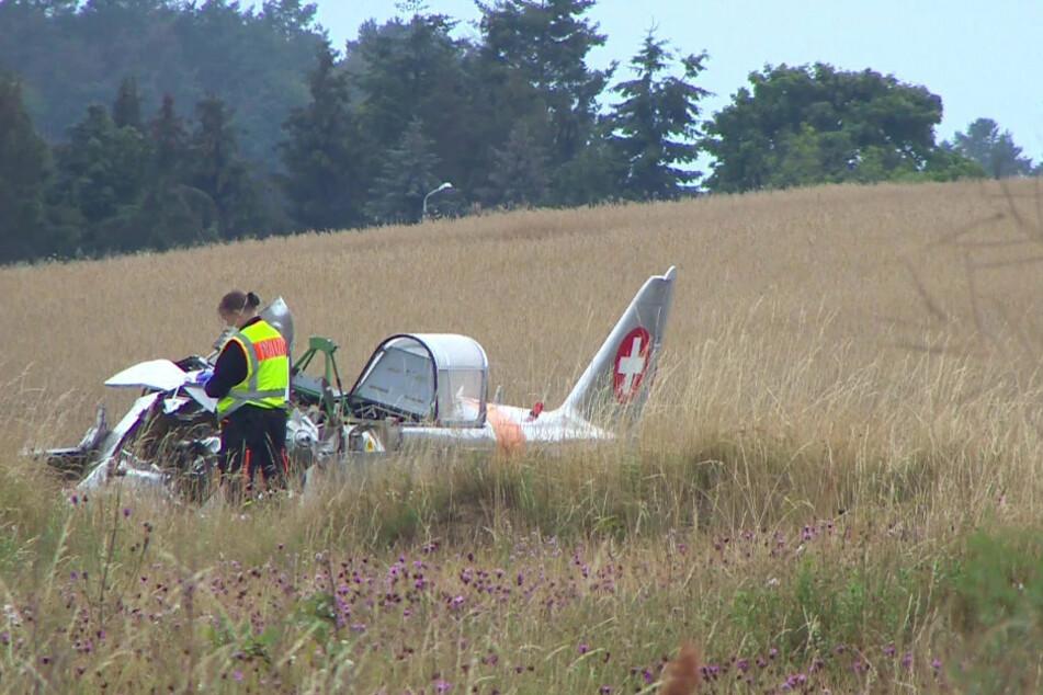 Eine Polizistin steht am Wrack des abgestürzten Kleinflugzeuges auf der Ostseeinsel Usedom.