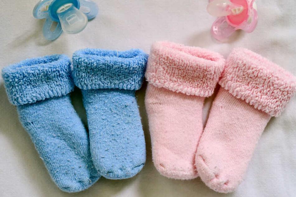 Rosa und blaue Söckchen und dazu die farbigen Nuckel für ein Mädchen und einen Jungen liegen in einem Babybett. (Archivbild)