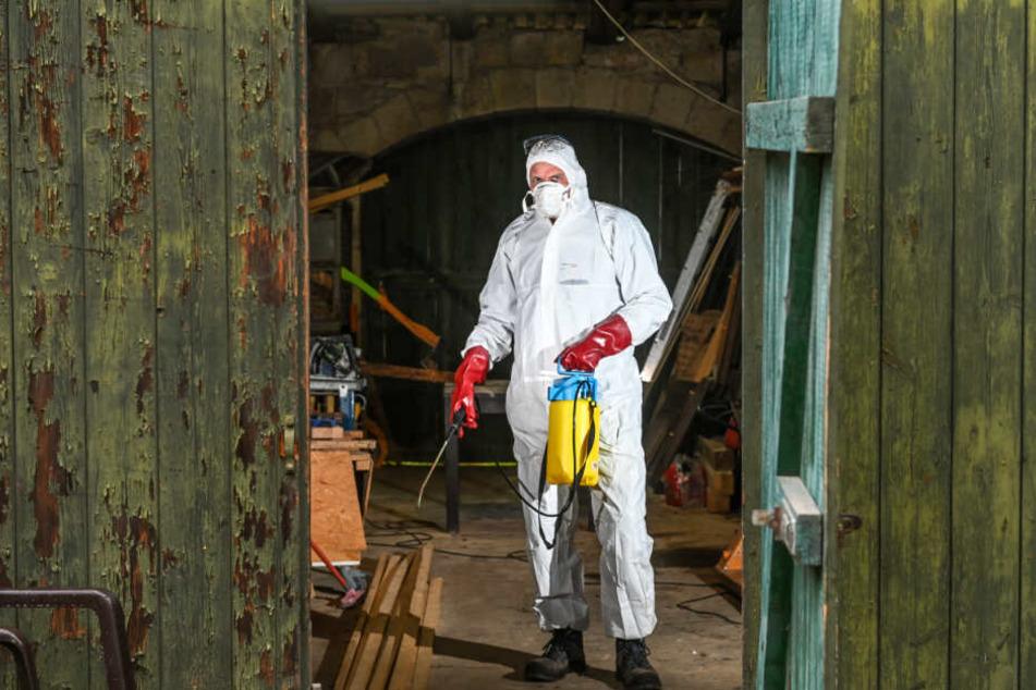 Tatortreiniger Thomas Pauland (53) in seinem Schutzanzug und Druckspritze zur Reinigung.