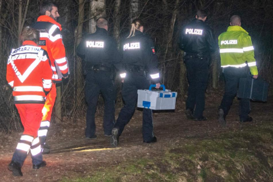 Polizisten, Notärztin und Rettungsdienstmitarbeiter gehen auf einem Weg am Einsatzort in einem Waldstückchen in Winsen.
