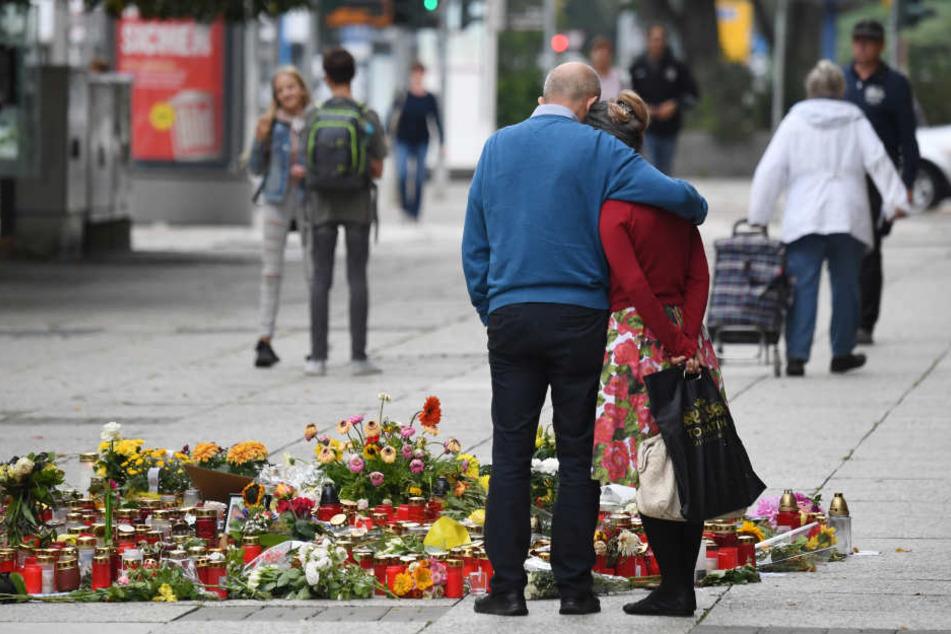 Passanten stehen am Tatort, an dem zahlreiche Blumen und Kerzen niedergelegt wurden.