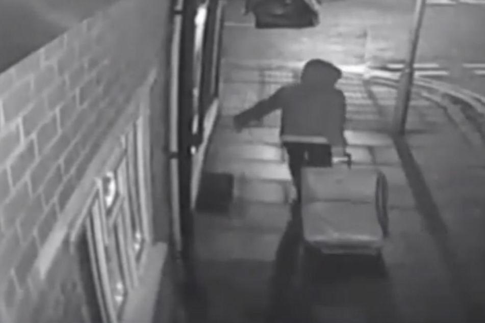 Hier sieht man, wie der Mann die Leiche durch die Straße zieht.