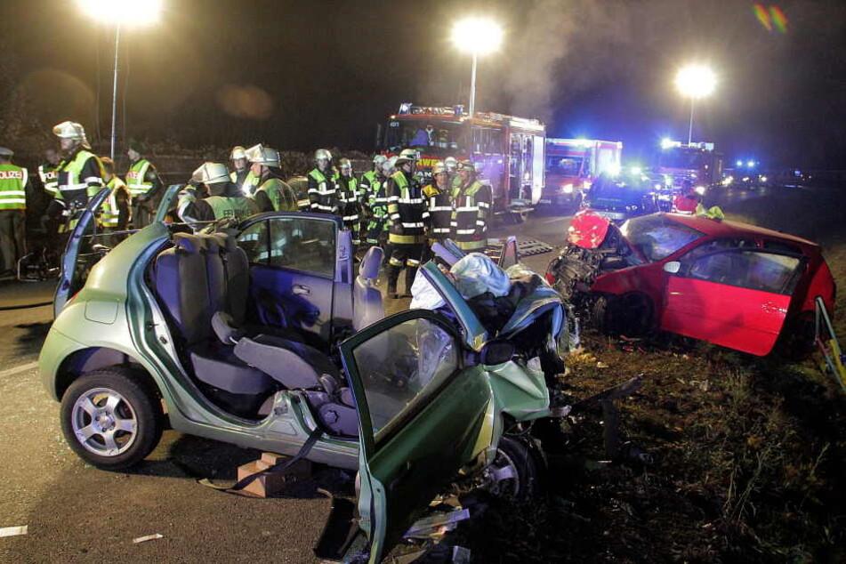 Rettungskräfte und zwei zerstörte Fahrzeuge stehen an einer Unfallstelle. Zwei junge Frauen starben bei dem Unfall, zwei weitere Frauen wurden schwer verletzt. (Archivbild)