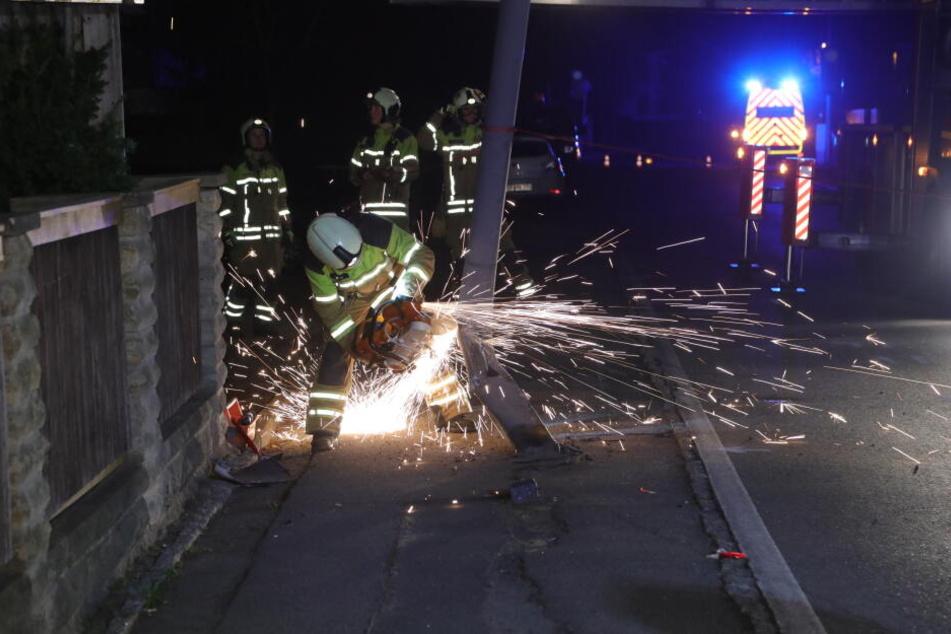 Einsatzkräfte mussten den beschädigten Lichtmast zersägen und anschließend fällen.