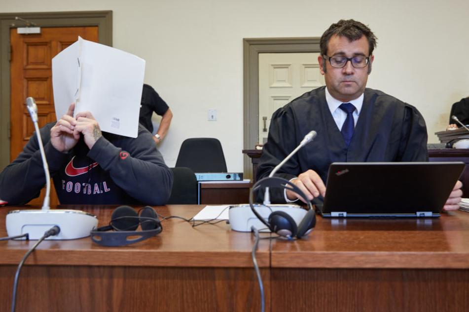 Der Angeklagte (links) und sein Anwalt sitzen in einem Sitzungssaal des Strafjustizgebäudes.