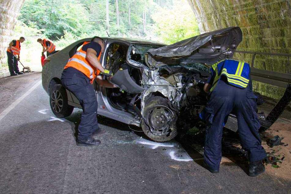 Einsatzkräfte an der Unfallstelle betrachten das völlig zerstörte Auto.