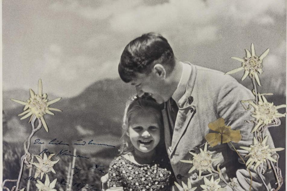 """Das Foto aus dem Jahr 1933, das von Alexander Historical Auctions veröffentlichtet wurde, zeigt Adolf Hitler, der das jüdische Mädchen Bernhardine """"Rosa"""" Nienau umarmt."""