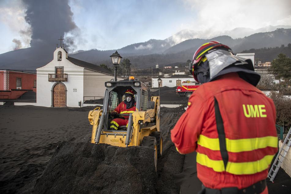 Einsatzkräfte des Militärs entfernen schwarze Asche vom Vulkan auf La Palma, der hinter einer Kirche auf der Kanareninsel La Palma weiter Lava ausstößt.