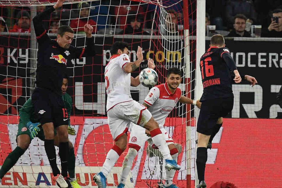 Lukas Klostermann (r.) schießt, Abwehrspieler Kaan Ayhan dreht sich nach links hinten weg, bekommt den Ball an den Unterarm und verursachte so einen Elfmeter.