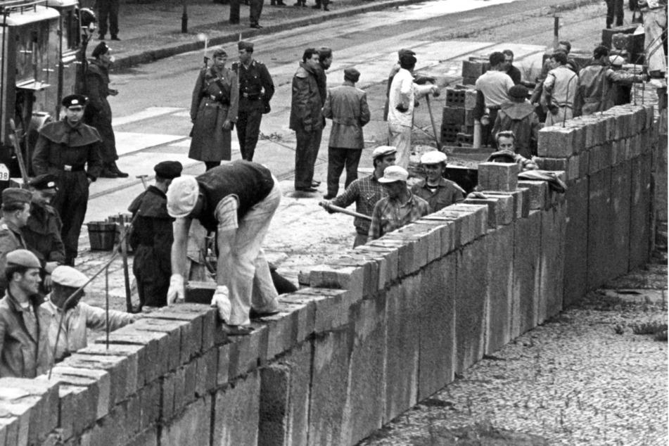Unter der Aufsicht von bewaffneten Volkspolizisten errichtet eine Ostberliner Maurerkolonne am 18.8.1961 an der sowjetisch-amerikanischen Sektorengenze am Potsdamer Platz eine Mauer. (Archivbild)